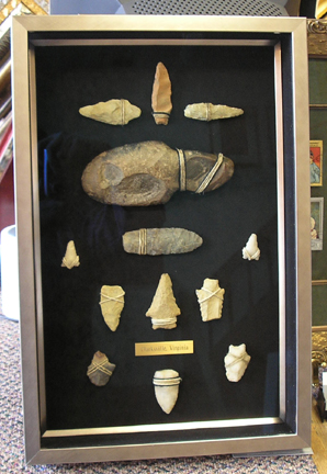 A great collection of Arrowheads and Axes sewn into the shadow box with twine and rope